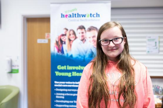 Young girl standing in front of a Healthwatch sign