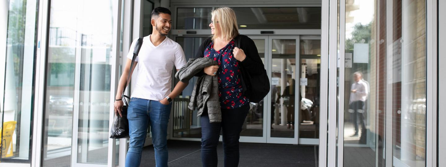 A man and women talking and walking out of hospital and talking